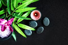 Thai Spa. Top view of hot stones setting for massage treatment and relax with purple orchid on blackboard stock photography