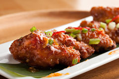 Thai Spicy Chicken Wings. Thai style spicy chicken wings appetizer on a contemporary white plate Royalty Free Stock Photo