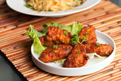 Thai Spicy Chicken Wings. Thai style spicy chicken wings on a round white plate Royalty Free Stock Photo