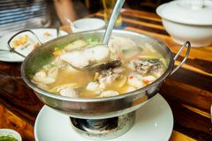 Thai spicy freshwater fish soup with herbs, served in big bowl. Tom Yam Pla. Thai famous street local food. recommended menu for t stock image