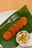 Thai spicy fried fish cake. Thai appetizer,  Spicy fried fish cake (Tod Mun Pla) served with cucumber in sweet sauce Royalty Free Stock Image