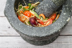 Thai spicy green papaya salad. In traditional marble mortar and pestle on wooden table Royalty Free Stock Photography