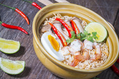 Thai spicy instant noodle. With shrimps and boiled egg on wood background royalty free stock image