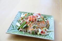 Thai spicy mixed salad. On wooden background stock photography