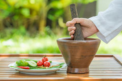 Thai spicy papaya salad ,famous thai menu. Woman pounds wooden pestle and mortar cooking Som tum,thai spicy papaya salad royalty free stock photo