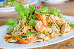 Thai Spicy salad with chicken, shrimp, fish and vegetables. On white dish Royalty Free Stock Photography