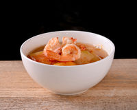 Thai spicy soup (Kaeng Som with shrimp). Thai spicy soup (Kaeng Som with shrimp) on the wooden floor Stock Image