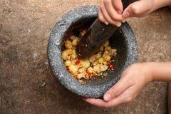 Thai spicy star gooseberry salad. Cooking Thai spicy star gooseberry salad by pounding in rock mortars Royalty Free Stock Photo