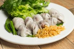 Thai steamed rice-skin dumpling with deep fried garlic and chilli in white dish on wood table. Thai steamed rice-skin dumpling with deep fried garlic and chilli royalty free stock image