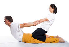 Thai stretch. Middle aged man receiving massage by therapist in traditional Thai stretch position Stock Photos