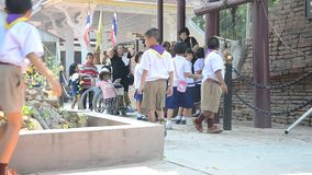 Thai student boys and girls scouts walking and pray buddha statue stock video