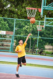 Thai student is doing a layup shoot in public basketball court. BANGKOK, THAILAND - 22 JULY 2014: Thai student is doing a layup shoot in public basketball court Stock Photography
