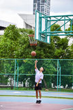 Thai student is doing a layup shoot in public basketball court. BANGKOK, THAILAND - 22 JULY 2014: Thai student is doing a layup shoot in public basketball court Royalty Free Stock Images