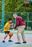 Thai student is practicing basketball with a coach in public cou Stock Image