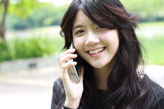 Thai student teen beautiful girl Answer the phone and smile stock photo