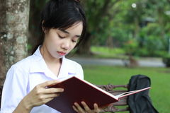 Thai student teen beautiful girl read a book sitting in park. Stock Photo