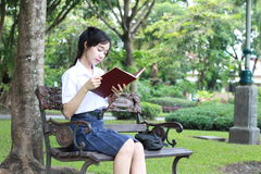 Thai student teen beautiful girl read a book sitting in park. Stock Photos