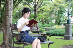 Thai student teen beautiful girl read a book sitting in park. Stock Images