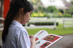 Thai student teen beautiful girl read a book sitting in park. Royalty Free Stock Images