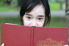 Thai student teen beautiful girl read a book sitting in park. Royalty Free Stock Photography