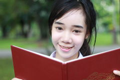 Thai student teen beautiful girl read a book sitting in park. Stock Photography
