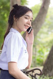 Thai student teen beautiful girl using her phone and smile. Royalty Free Stock Images