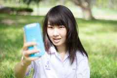 Thai student teen beautiful girl using her smart phone Selfie in park. Royalty Free Stock Image