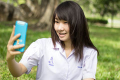 Thai student teen beautiful girl using her smart phone Selfie in park. Stock Photo