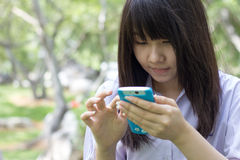 Thai student teen beautiful girl using her smart phone sitting in park. Stock Images