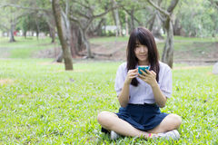 Thai student teen beautiful girl using her smart phone sitting in park. Stock Photo