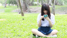 Thai student teen beautiful girl using her smart phone sitting in park. stock footage