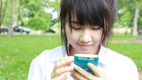 Thai student teen beautiful girl using her smart phone sitting in park. stock video footage