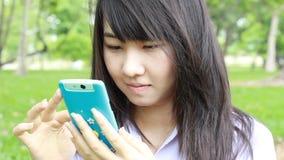 Thai student teen beautiful girl using her smart phone sitting in park. stock video