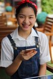 Thai student teen beautiful girl using her smart phone and smile. Royalty Free Stock Image