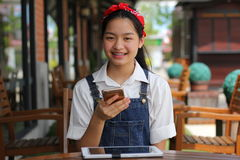 Thai student teen beautiful girl using her smart phone and smile. Stock Images