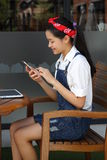 Thai student teen beautiful girl using her smart phone and smile. Stock Photo
