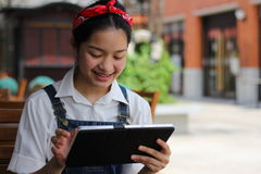 Thai student teen beautiful girl using her tablet. Stock Photography