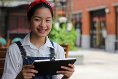 Thai student teen beautiful girl using her tablet. Stock Photos