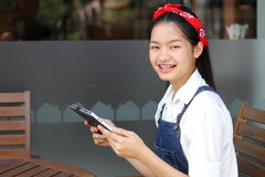 Thai student teen beautiful girl using her tablet. Royalty Free Stock Photos