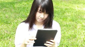 Thai student teen beautiful girl using her tablet sitting in park. stock video