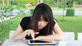 Thai student teen beautiful girl using her tablet sitting in park. stock video footage