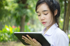 Thai student teen beautiful girl using her tablet sitting in park. Stock Image