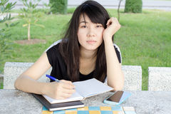 Thai student teen beautiful girl write a book sitting in park. Stock Photo