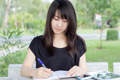 Thai student teen beautiful girl write a book sitting in park. Royalty Free Stock Photography
