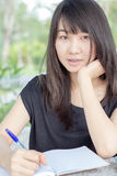 Thai student teen beautiful girl write a book sitting in park. Stock Photography