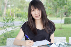 Thai student teen beautiful girl write a book sitting in park. Royalty Free Stock Photos
