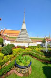 Thai stupa on the background of a Buddhist temple who drowned in the green landscape design. Thailand Stock Image