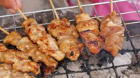 Thai style BBQ pork are grilled on the aluminium grid . Thai style BBQ pork fat are grilled on the aluminium grid with wood charcoal that some are burnt to royalty free stock photography