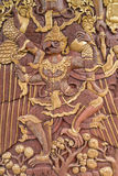 Thai style carving a garuda. Carving a garuda, Thai style carving on door in the thai temple Royalty Free Stock Photo