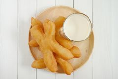 Thai style Chinese crullers in wooden plate with a glass of soy milk. royalty free stock images